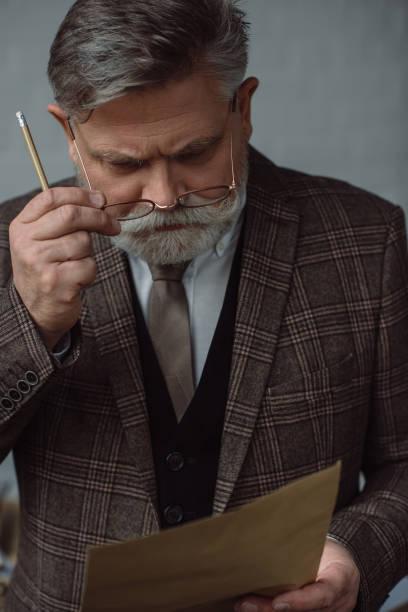 nachdenklicher senior mann mit bleistift und papier - gedichte zum ruhestand stock-fotos und bilder
