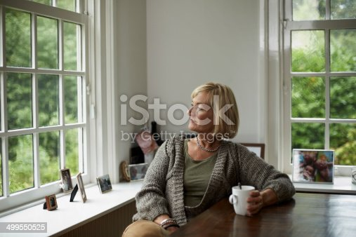 Thoughtful senior woman having coffee at table in cottage