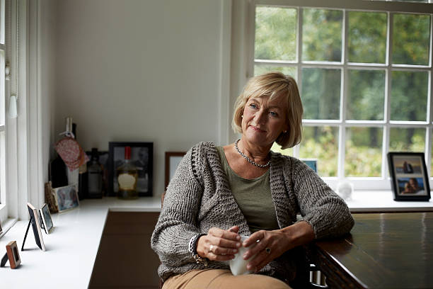 Thoughtful senior woman in cottage Thoughtful senior woman with coffee cup relaxing at table in cottage thinking photos stock pictures, royalty-free photos & images