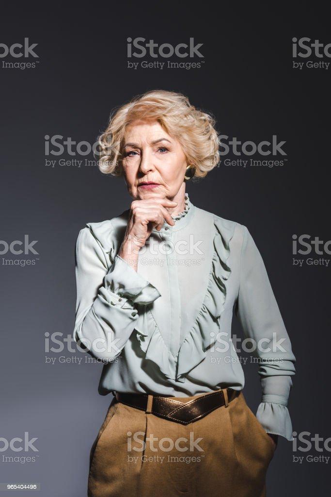 thoughtful senior woman in stylish shirt looking at camera on dark grey zbiór zdjęć royalty-free
