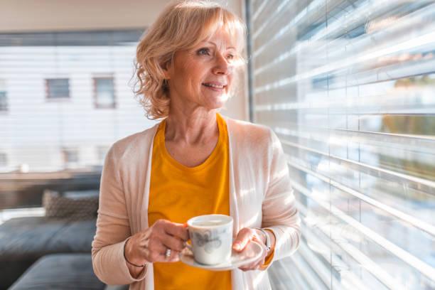 Nachdenkliche Seniorin schaut durch Fenster – Foto