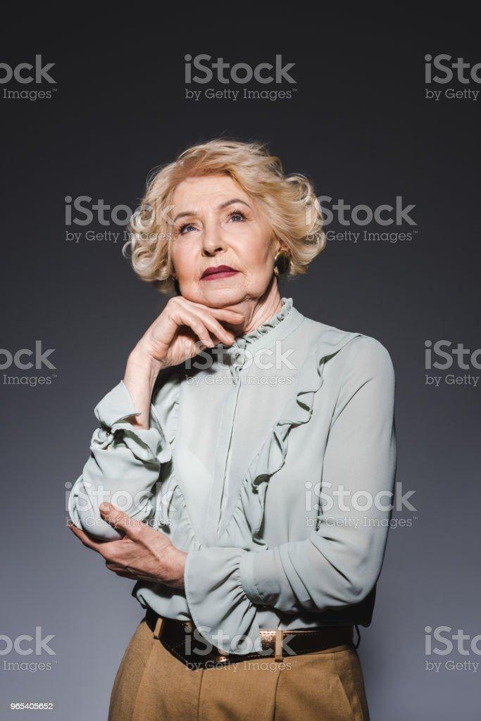thoughtful senior woman looking up on dark grey zbiór zdjęć royalty-free