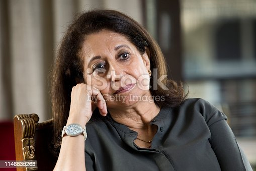Thoughtful senior woman relaxing on chair at home