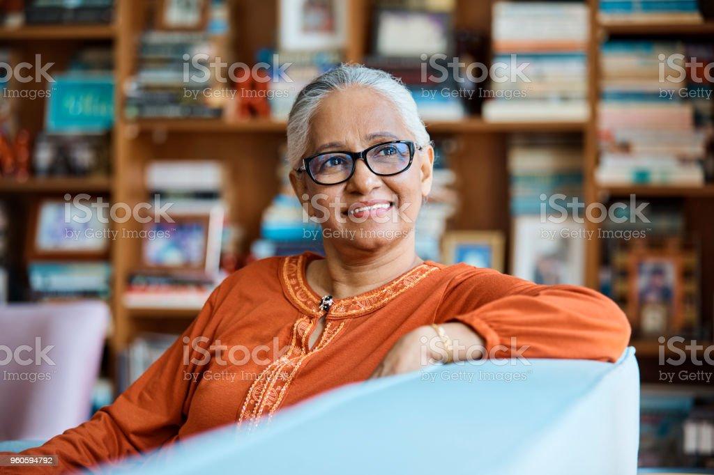 Nachdenklich senior Frau sitzt zu Hause auf sofa – Foto