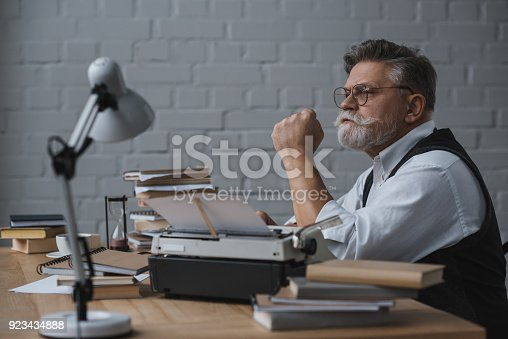 istock thoughtful senior writer sitting at workplace and looking away 923434888