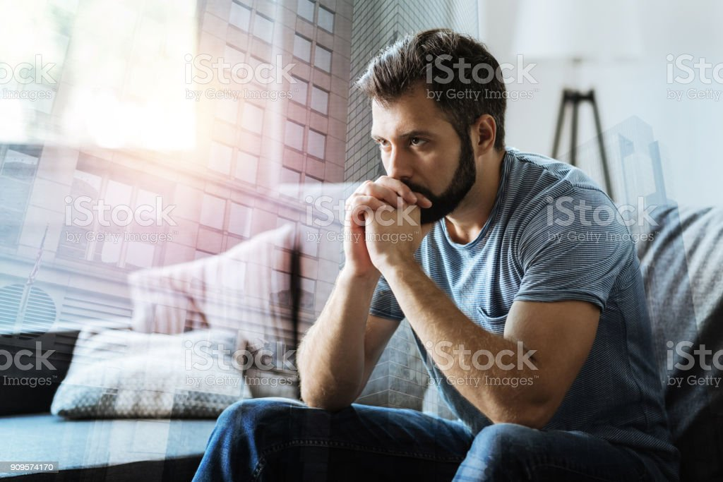 Thoughtful serious man sitting and thinking stock photo