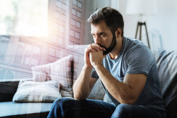 Thoughtful serious man sitting and thinking Think about it. Thoughtful serious beardful man sitting in the empty room holding hands near mouth and thinking. dependency stock pictures, royalty-free photos & images