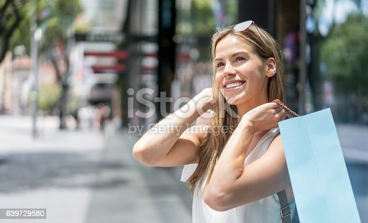 Portrait of a thoughtful shopping woman outdoors holding bags and looking very happy