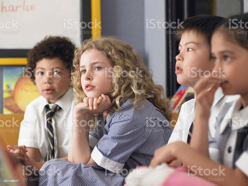 Thoughtful Students Sitting In Classroom stock photo