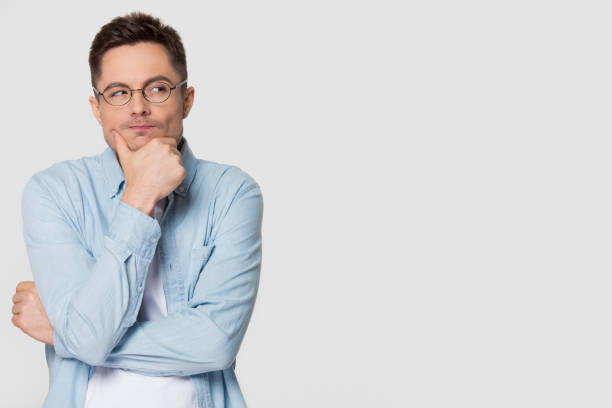 thoughtful suspicious young man looking aside at copyspace feeling skeptic - cynic stock pictures, royalty-free photos & images