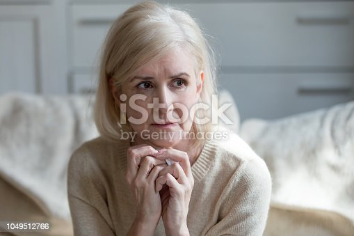 Thoughtful upset mature old lady feeling blue thinking of loneliness or grief, sad middle aged woman worried concerned about problems, serious depressed senior female widow crying grieving mourning