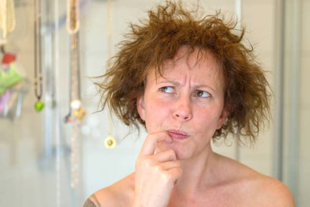 Thoughtful woman assessing her unruly tousled hair stock photo