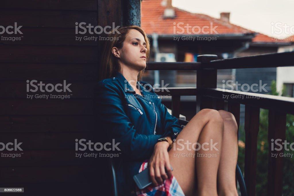 Mulher pensativa na varanda - foto de acervo