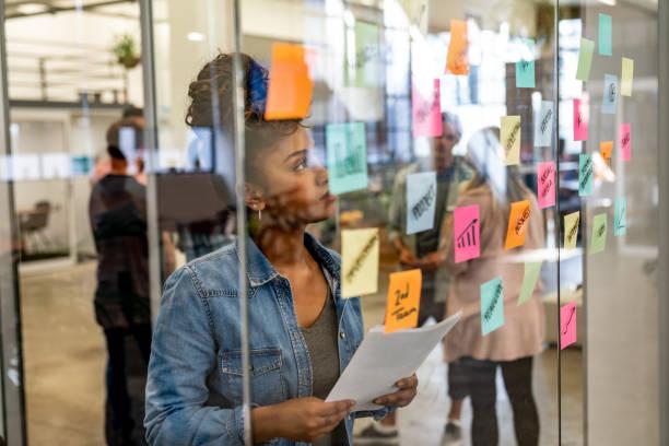 mujer pensativa de brainstorming en una oficina creativa - design thinking fotografías e imágenes de stock