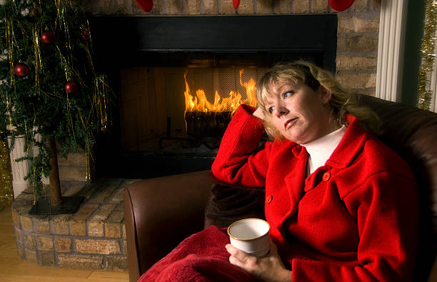 Thoughtful woman by the Fireplace at Christmas stock photo