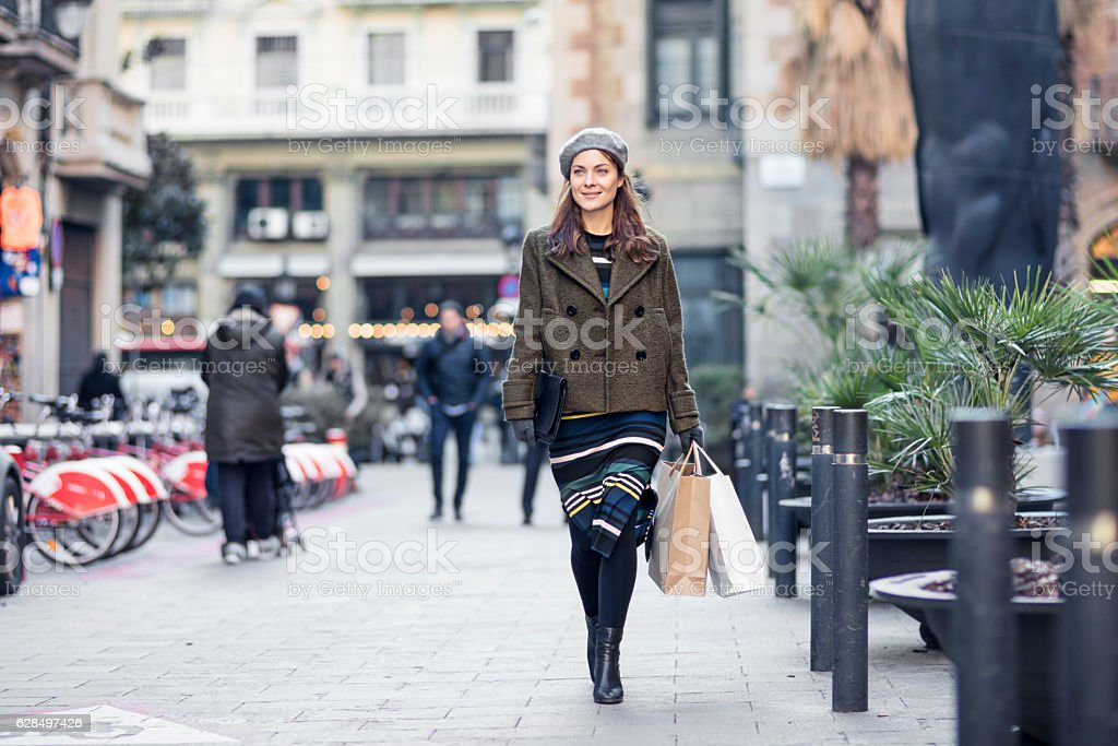 Thoughtful woman carrying shopping bags in city stock photo