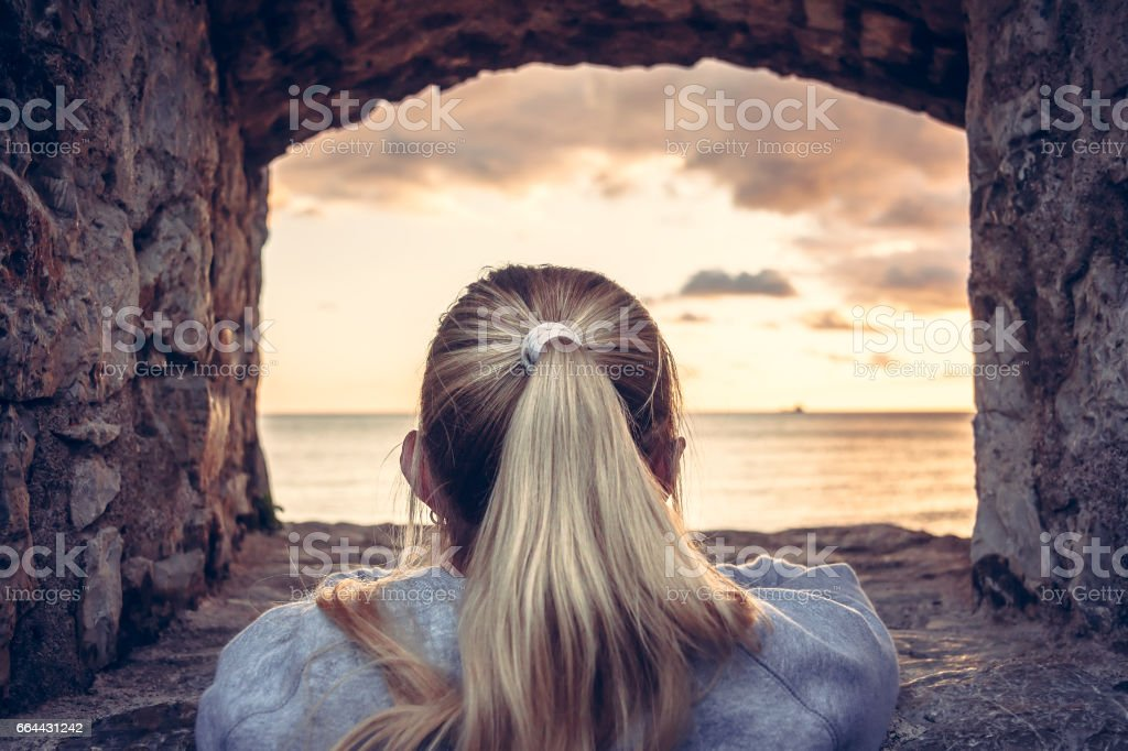 Thoughtful woman devoted into contemplation of beautiful sunset over sea through window of old castle with dramatic sky and perspective view. View from behind. Concept for forecasting and way forward stock photo