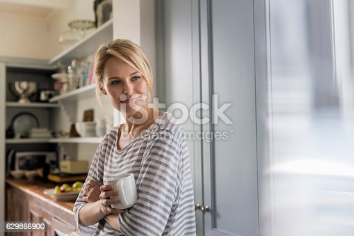 istock Thoughtful woman holding coffee mug by window 629866900