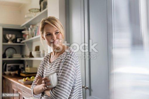 Thoughtful Woman Holding Coffee Mug By Window Stockfoto und mehr Bilder von 25-29 Jahre