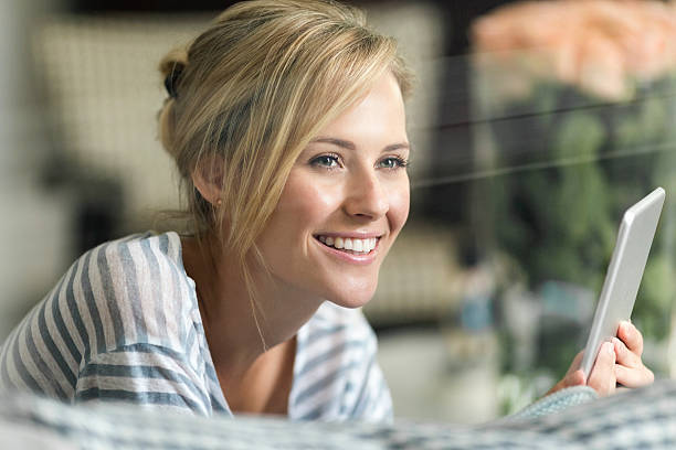 Thoughtful woman holding digital tablet at home - Photo