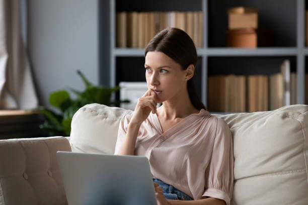 Thoughtful woman holding laptop, pondering ideas, sitting on couch at home stock photo