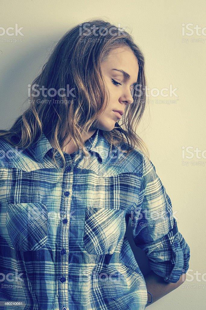 Thoughtful woman in check shirt stock photo