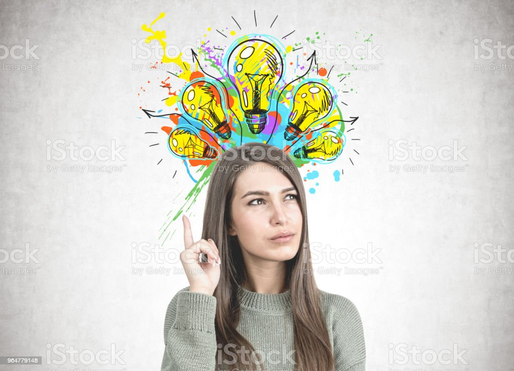 Thoughtful woman in green pointing up, creative royalty-free stock photo