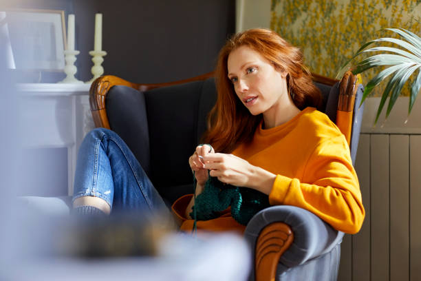 thoughtful woman knitting while sitting on chair - lavorare a maglia foto e immagini stock