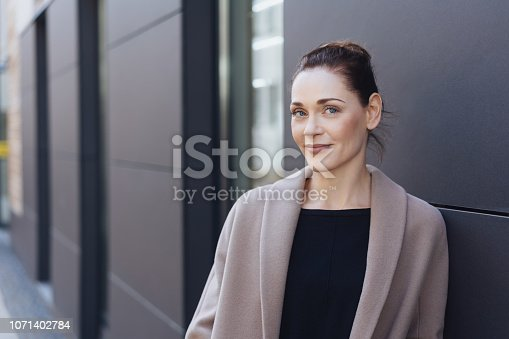 Thoughtful stylish young woman standing leaning against an exterior wall in town looking at camera with a smile with copy space