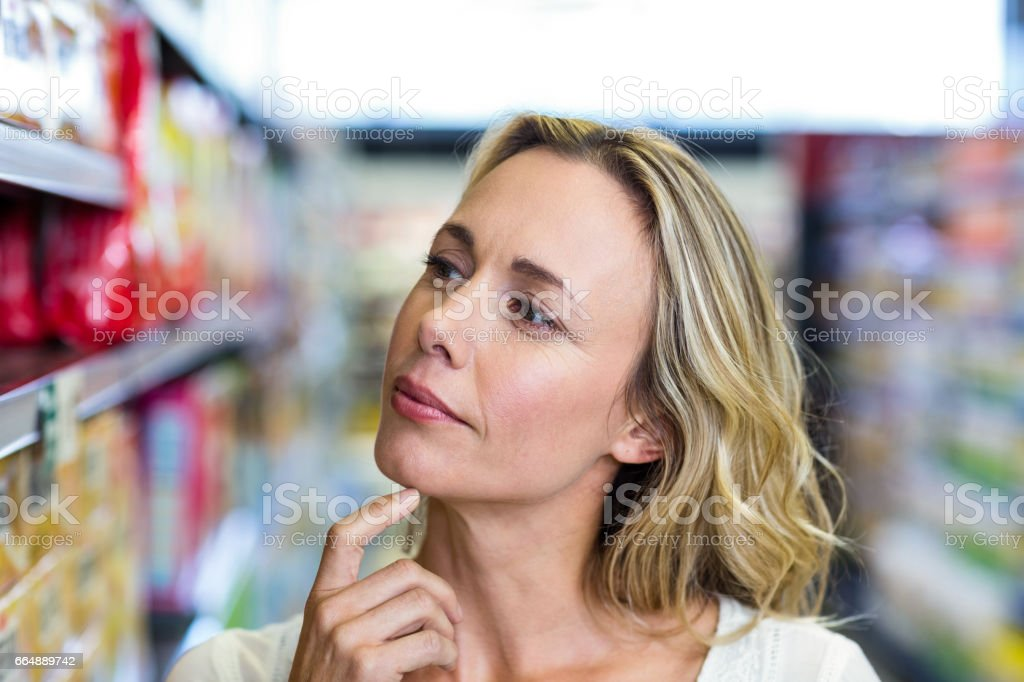 Thoughtful woman looking at shelves foto stock royalty-free