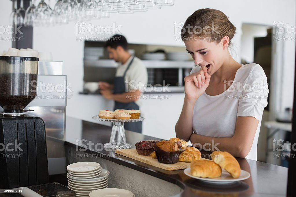 Thoughtful woman looking at sweet food stock photo