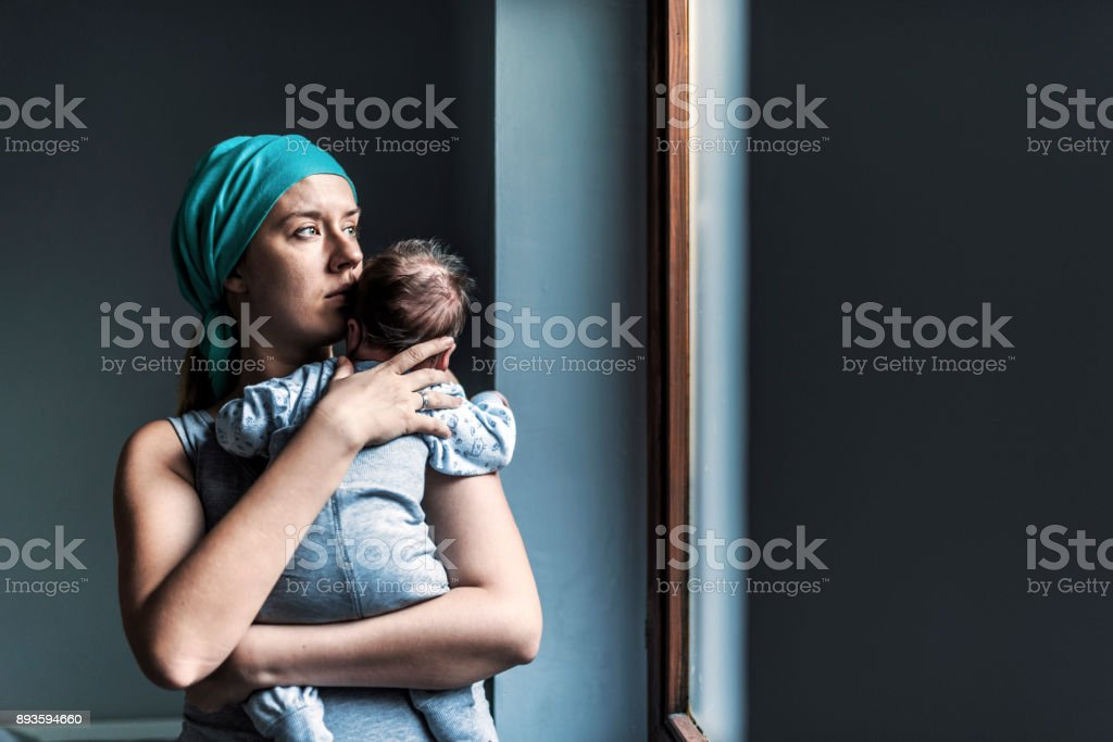 Thoughtful woman looking out the window while holding her son stock photo