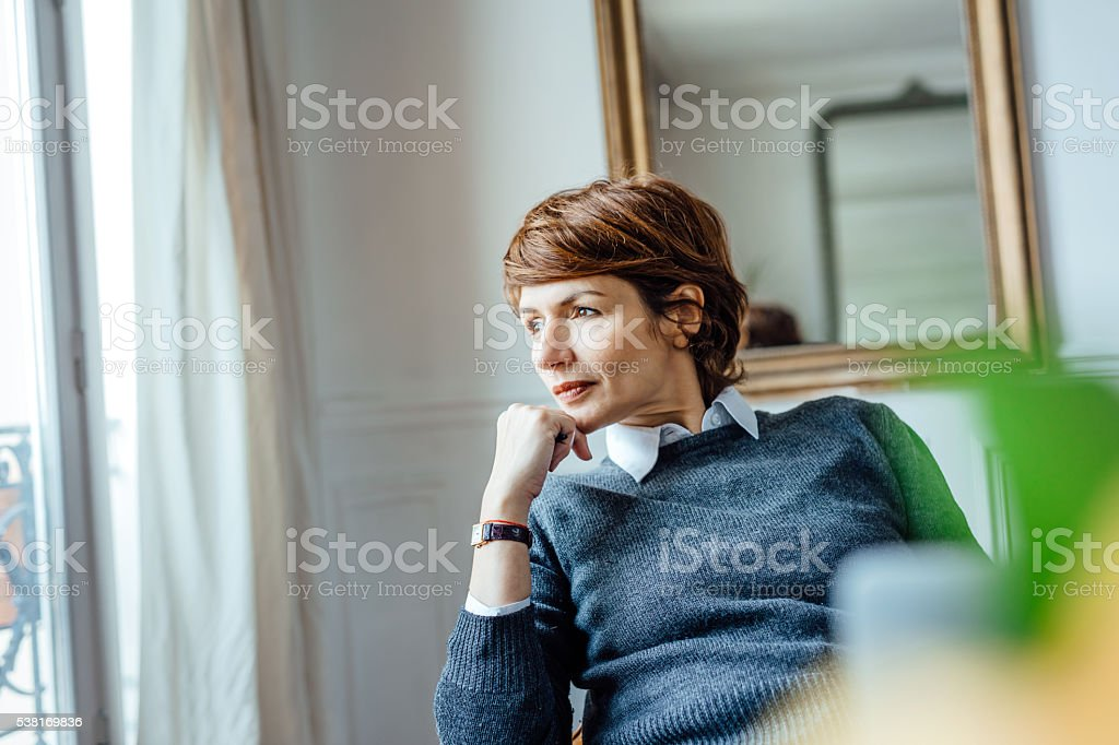 Thoughtful woman looking out window stock photo