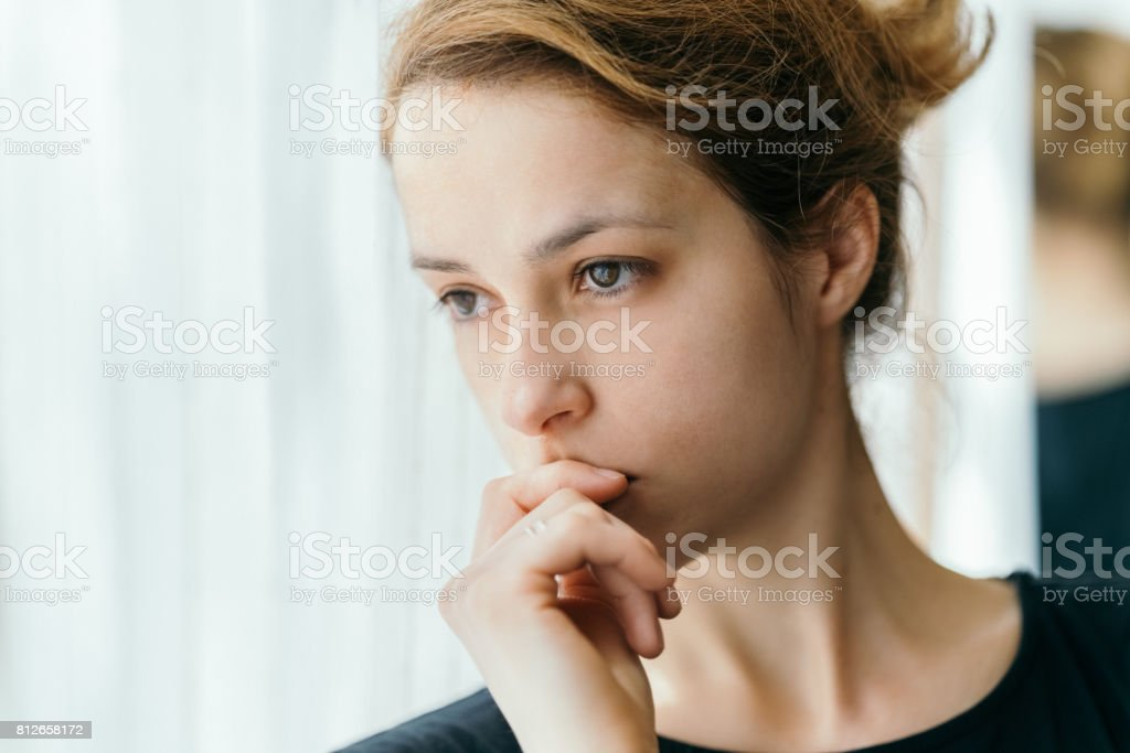 Thoughtful woman looking through the window stock photo