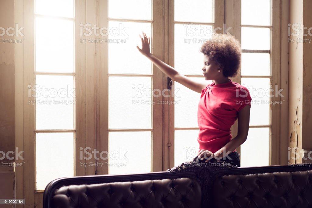 Thoughtful woman looking through window stock photo