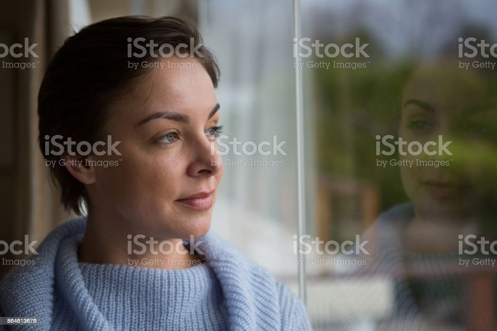 Thoughtful woman looking through window stock photo