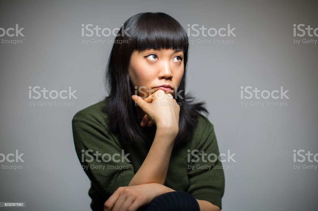 Thoughtful Woman Resting Against Gray Background stock photo