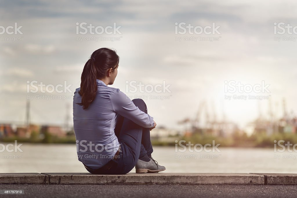 Thoughtful Woman Sits on Bench Facing at the River stock photo