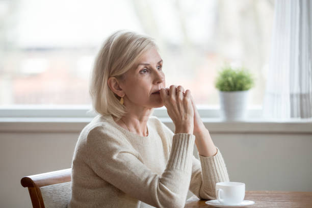 Thoughtful woman sitting at table with cup of tea Woman spend time at home alone sitting at table with cup of tea folds hands on chin lost in thoughts. Old lonely female has health problem or thinking about life, reminiscing the past relive memories apprehension stock pictures, royalty-free photos & images