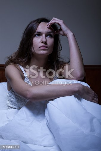 istock Thoughtful woman sitting in bed 526393221