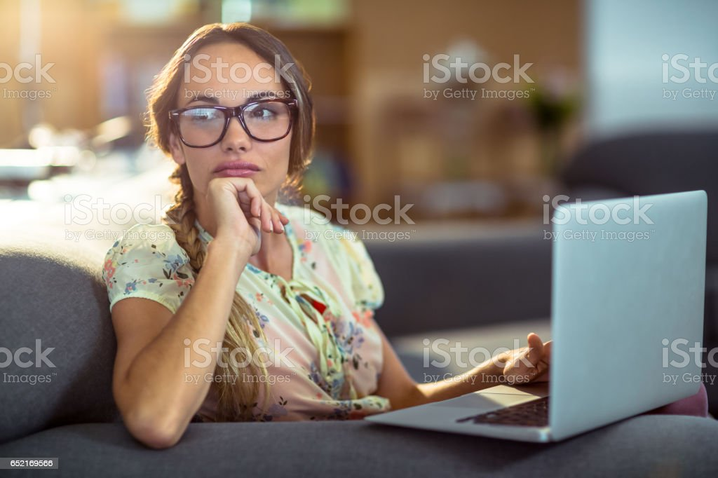 Thoughtful woman sitting on sofa and using laptop stock photo