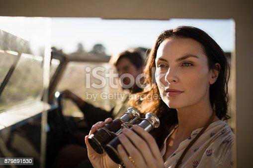 Thoughtful woman sitting with binoculars in vehicle during safari vacation