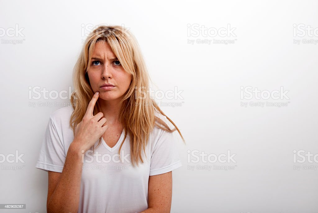 Thoughtful woman standing against white background royalty-free stock photo