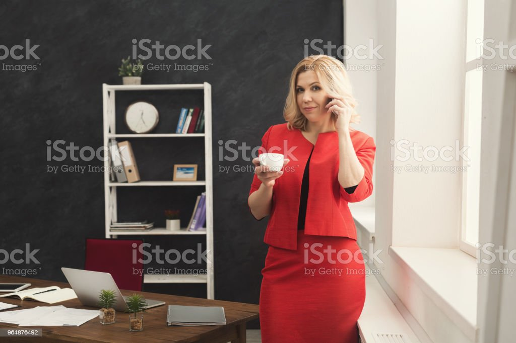 Thoughtful woman talking on phone at office royalty-free stock photo