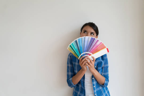 thoughtful woman thinking about the color of her house - decorating stock photos and pictures