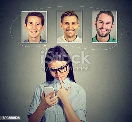 1125634038 istock photo Thoughtful woman thinking which man she likes the most using smartphone app 820859508
