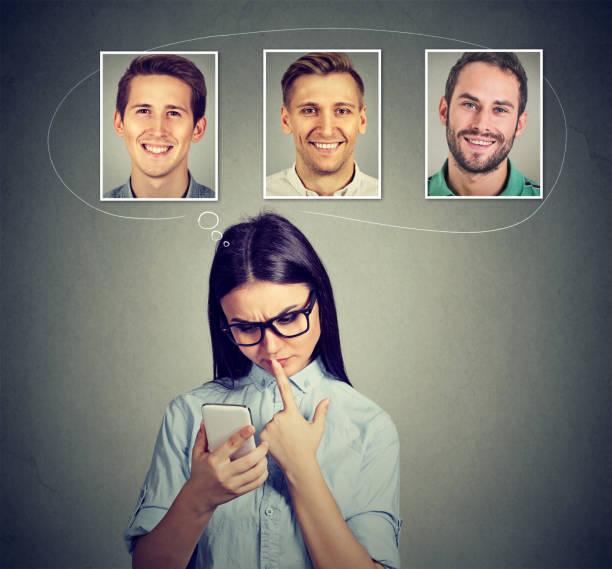 nachdenkliche frau denken, die der mensch sie mag am meisten mit smartphone-app - suche freundin stock-fotos und bilder