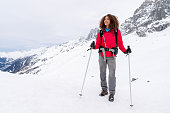 Thoughtful woman trekking in the snow mountains and looking happy smiling - alpinism concepts
