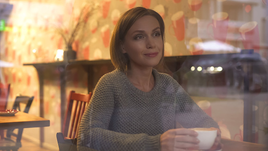 Thoughtful woman watching passersby through window of her favorite coffee house