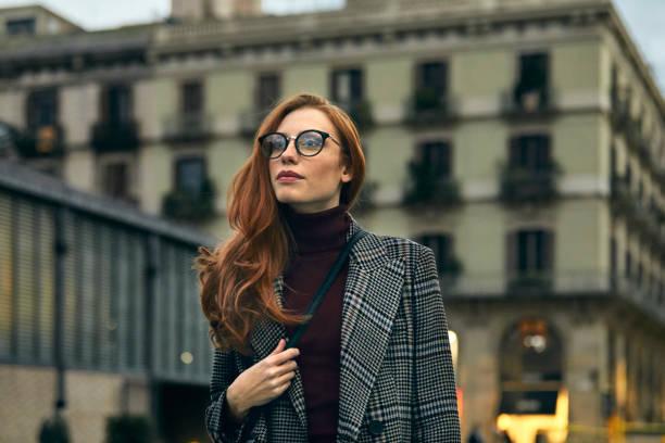 Nachdenkliche Frau mit langen Mantel zu Fuß in die Stadt – Foto